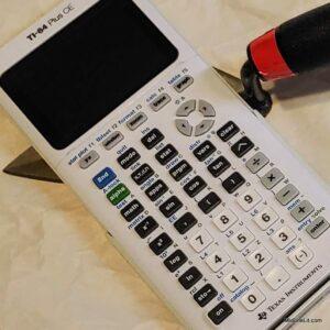 A TI-84 calculator atop a trowel
